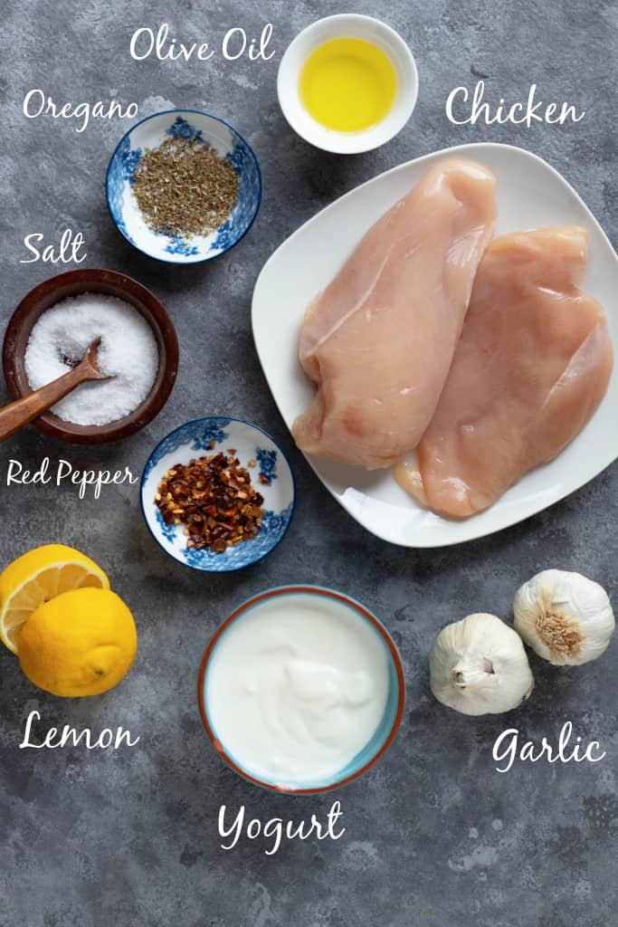 Ingredient shot for the recipe including olive oil, oregano, chicken, pepper, salt and lemon.