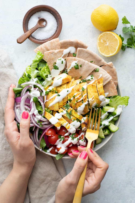 Drizzle chicken shawarma salad with yogurt tahini sauce.