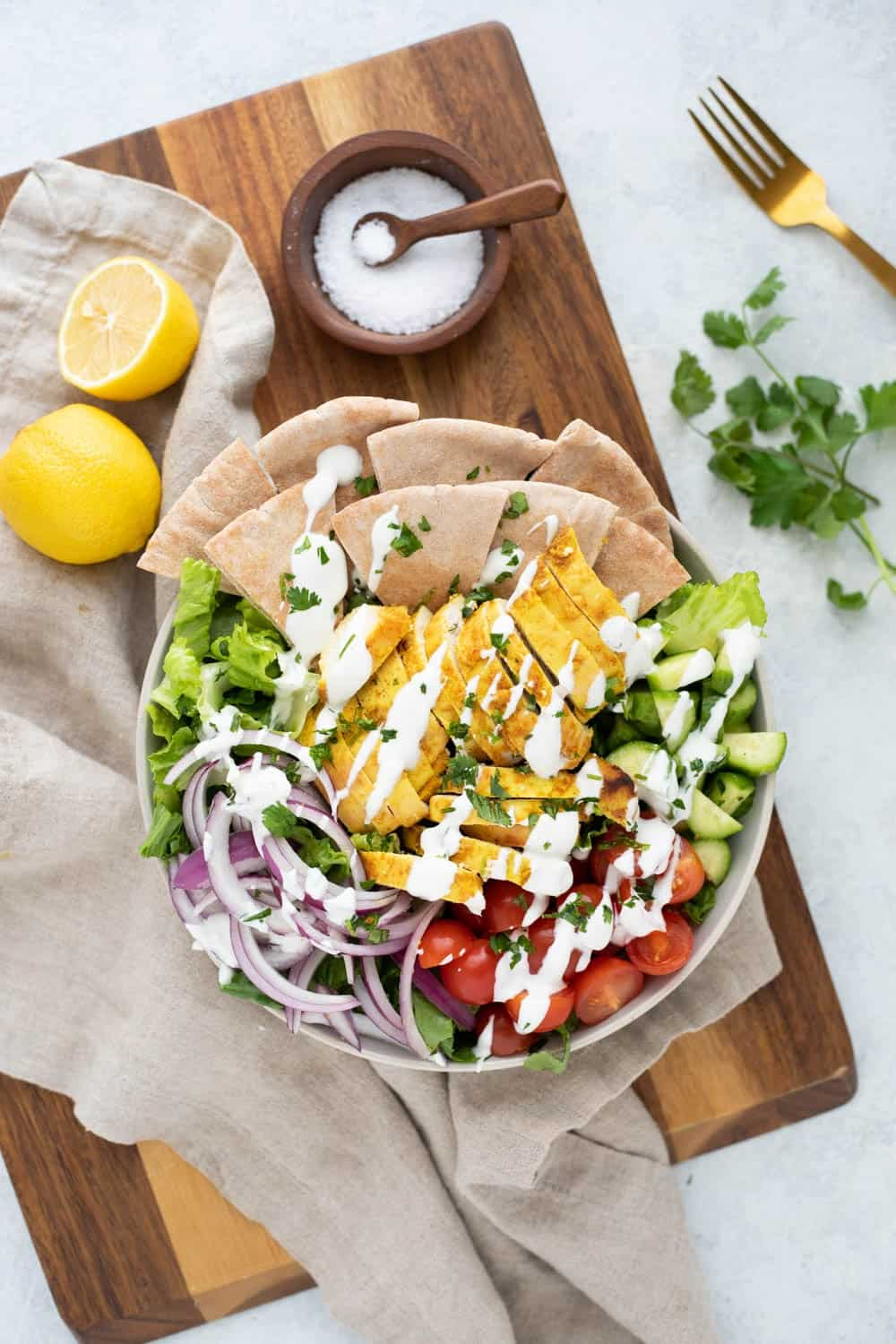A bowl of chicken shawarma salad topped with yogurt sauce.