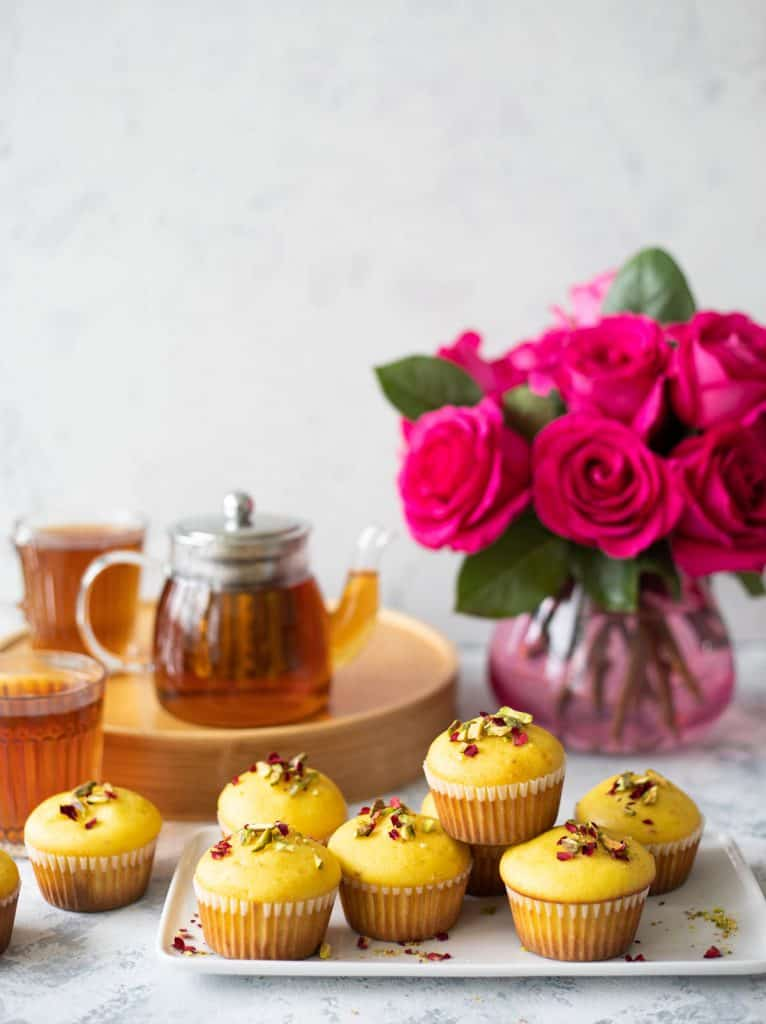 Persian love muffins on a plate with a vase of flowers.