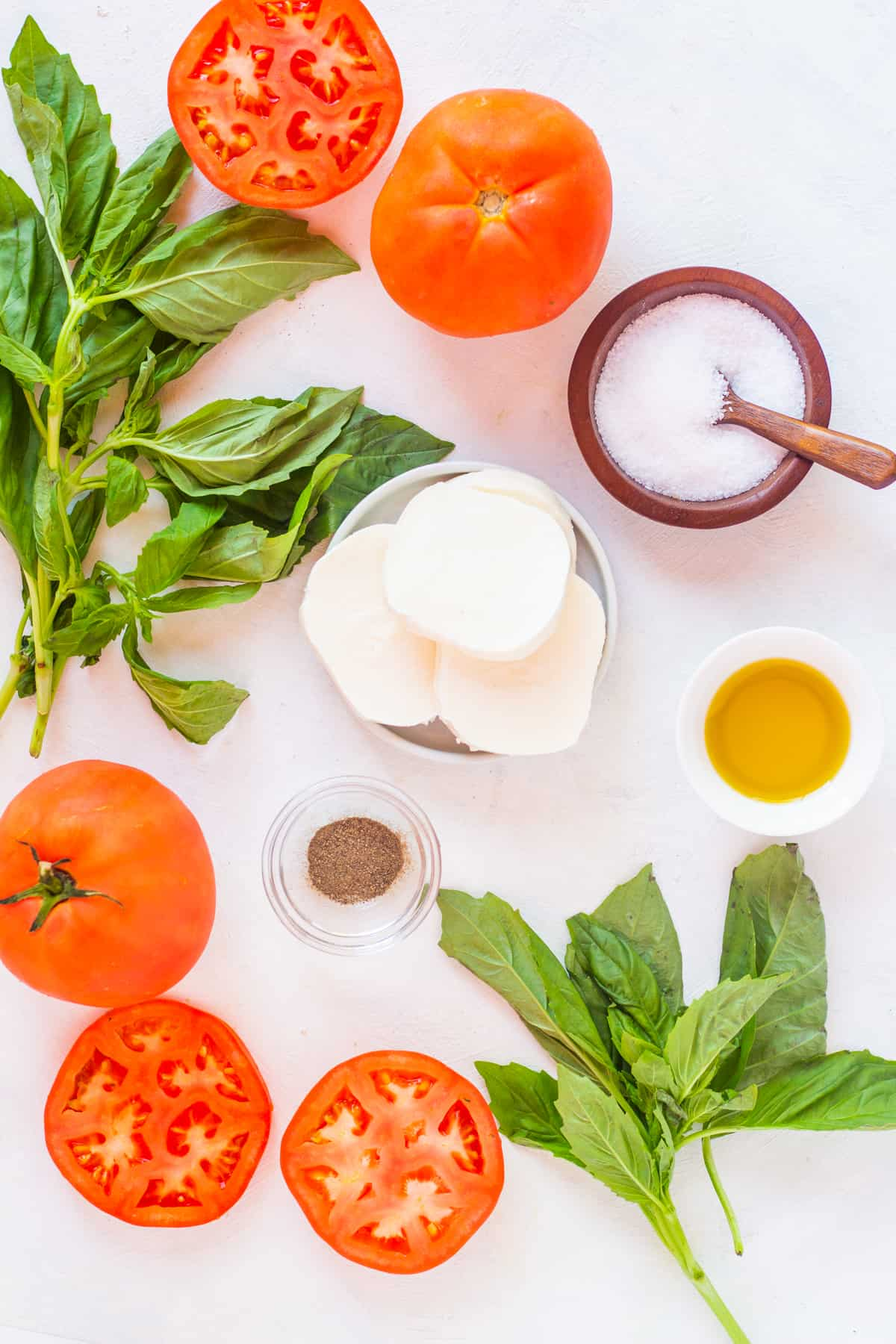 To make this Italian salad, you need tomatoes, mozzarella, basil, olive oil, salt and pepper.