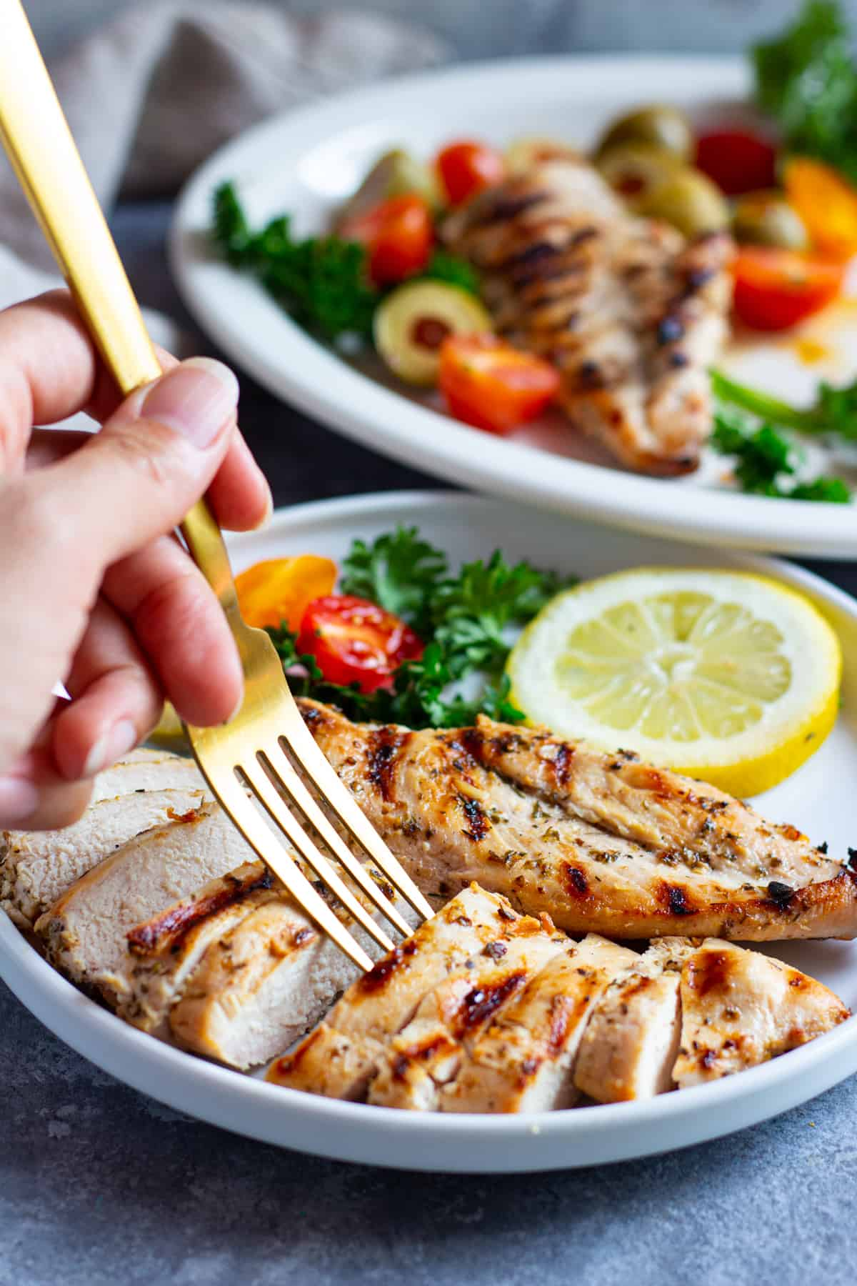 Greek grilled chicken sliced and served on a plate with lemon and herbs.