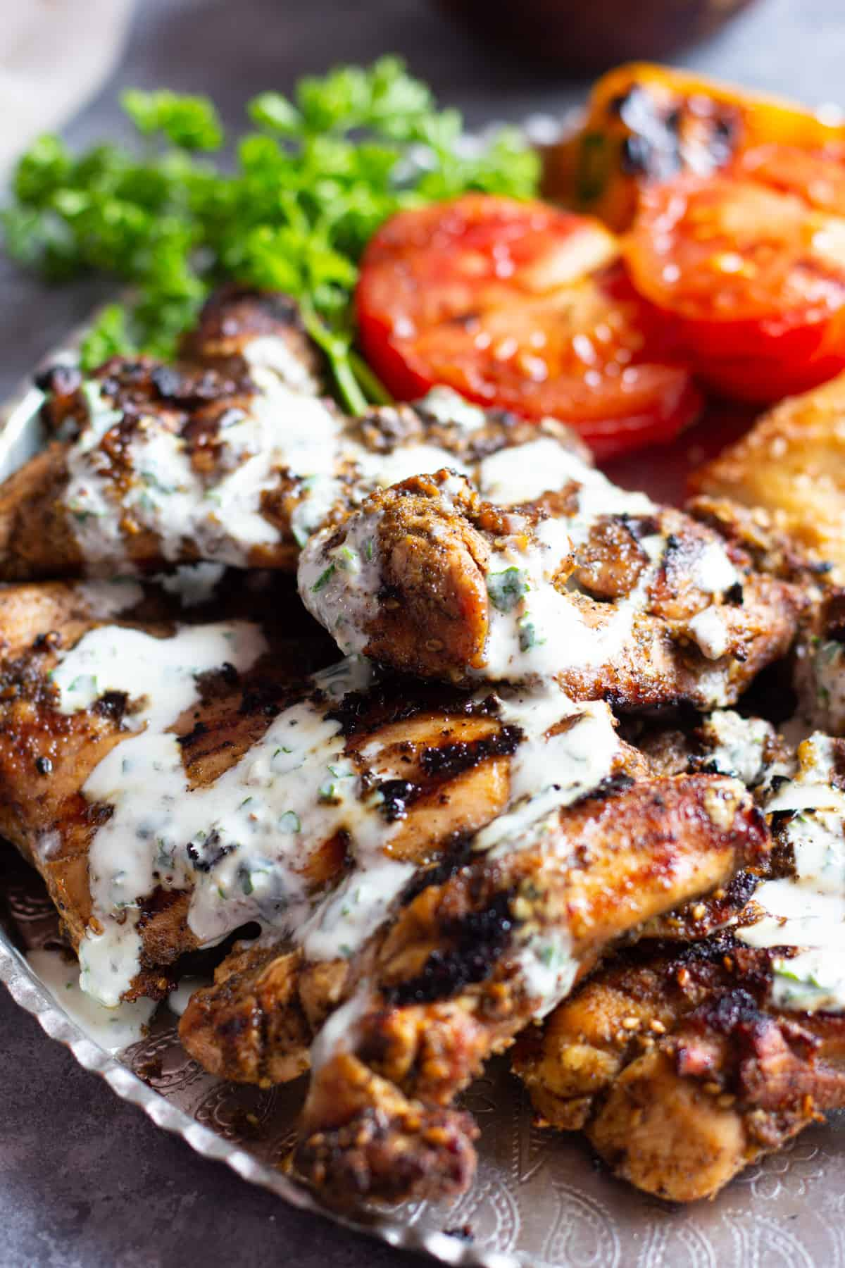 Zaatar chicken served with yogurt sauce on a platter with grilled tomatoes.