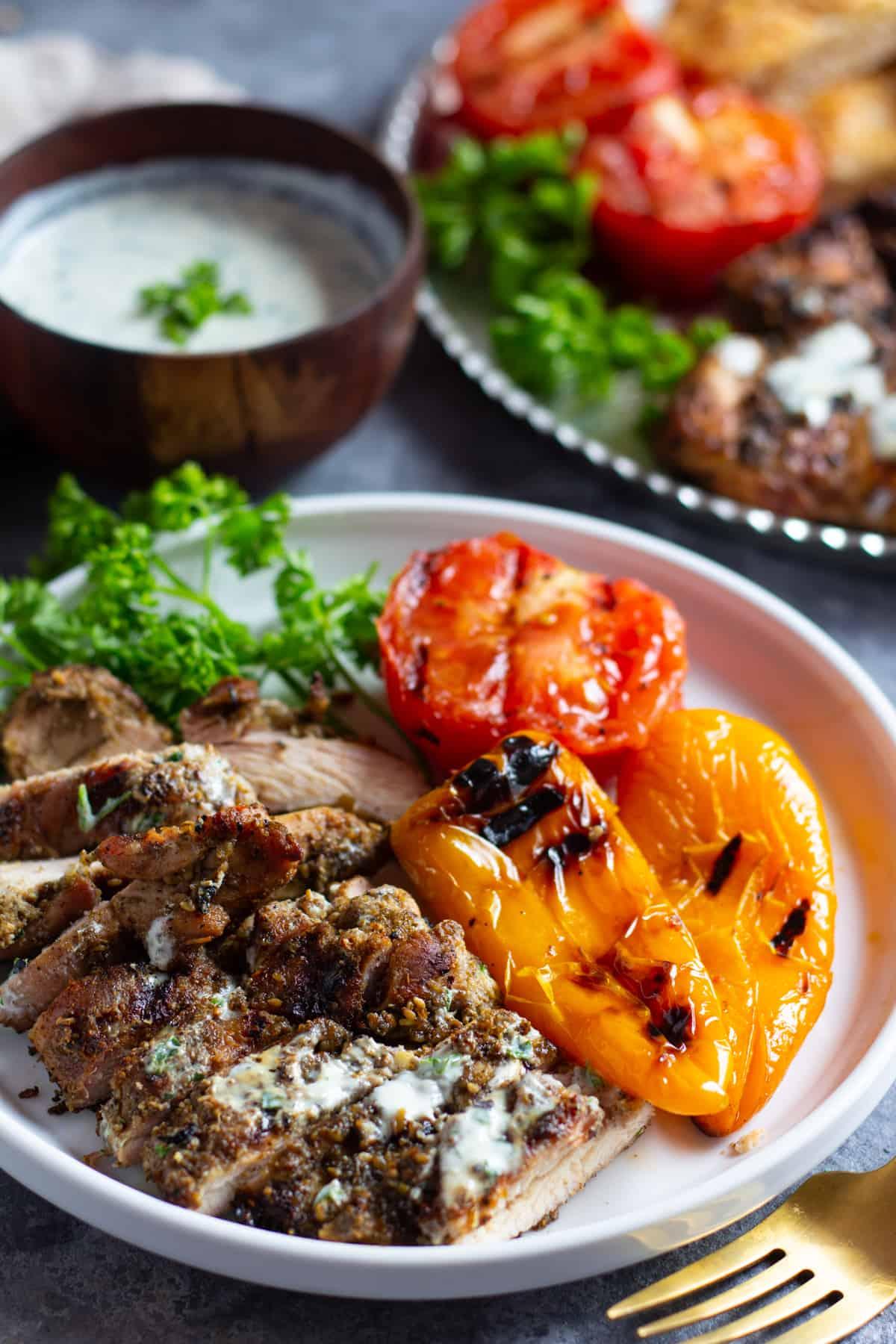 Serve grilled zaatar chicken with grilled vegetables and a herb yogurt sauce.