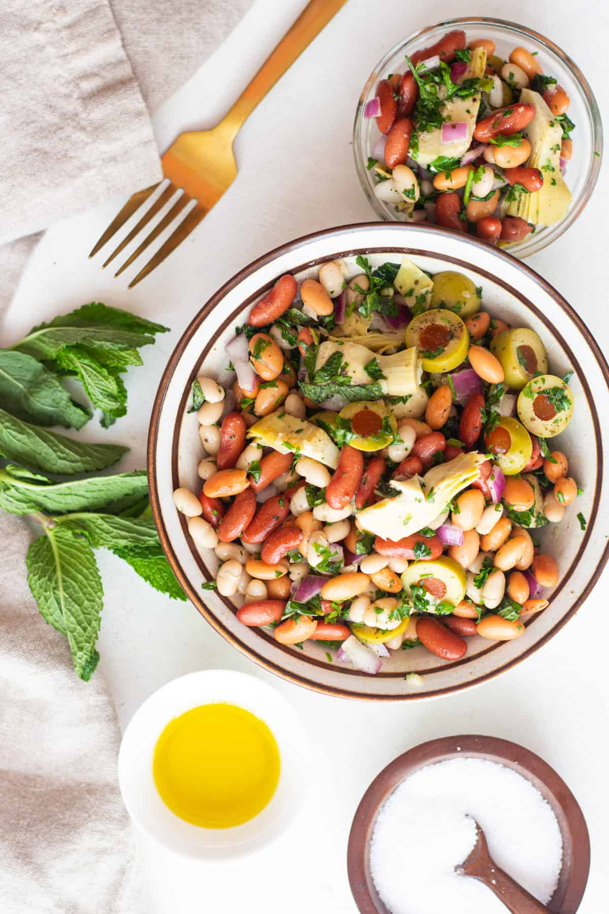 Two bowls of Mediterranean bean salad with mint and olive oil.