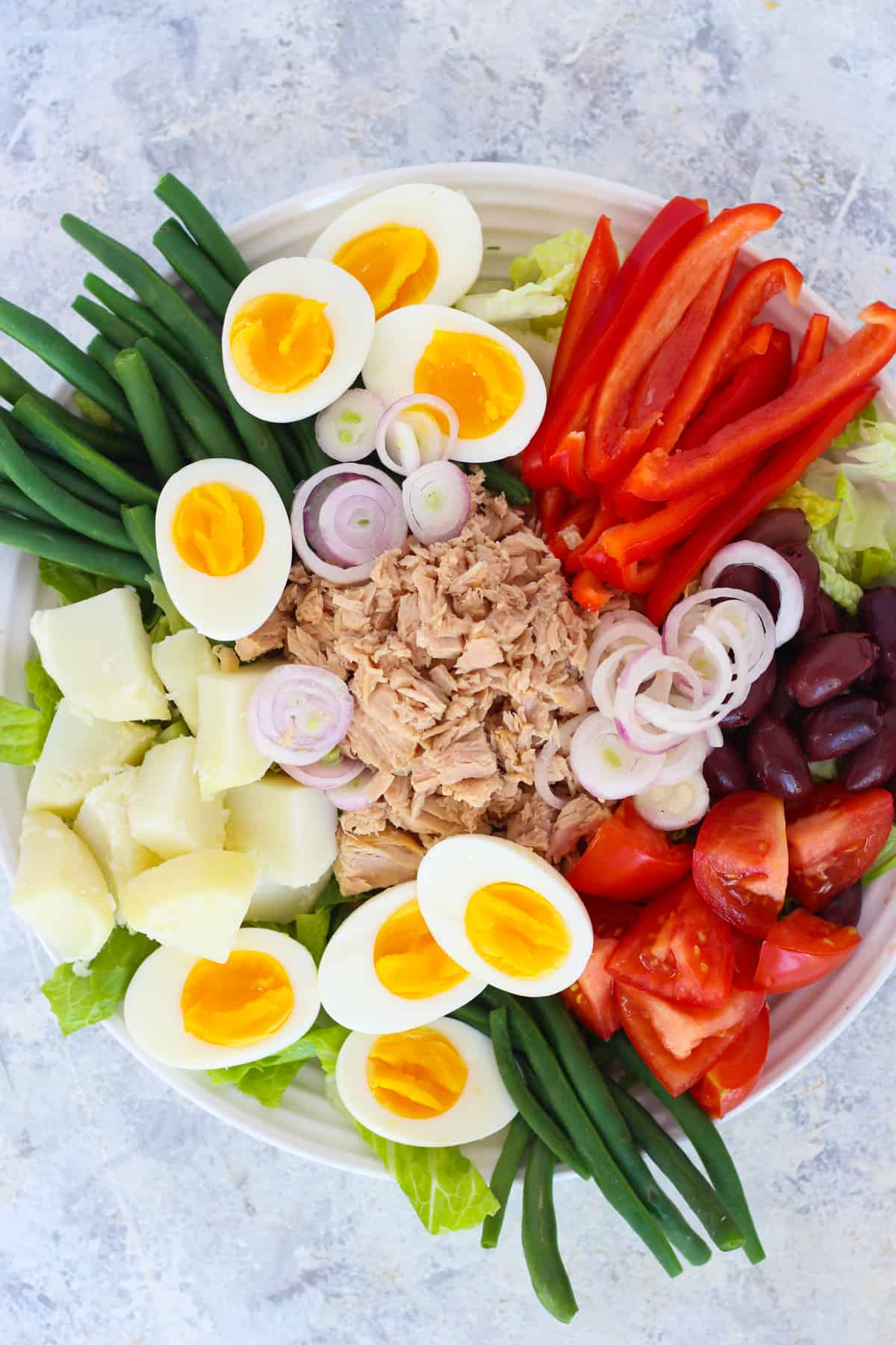 Nicoise salad is a French salad that is composed. The ingredients are arranged beautifully on a bed of lettuce.