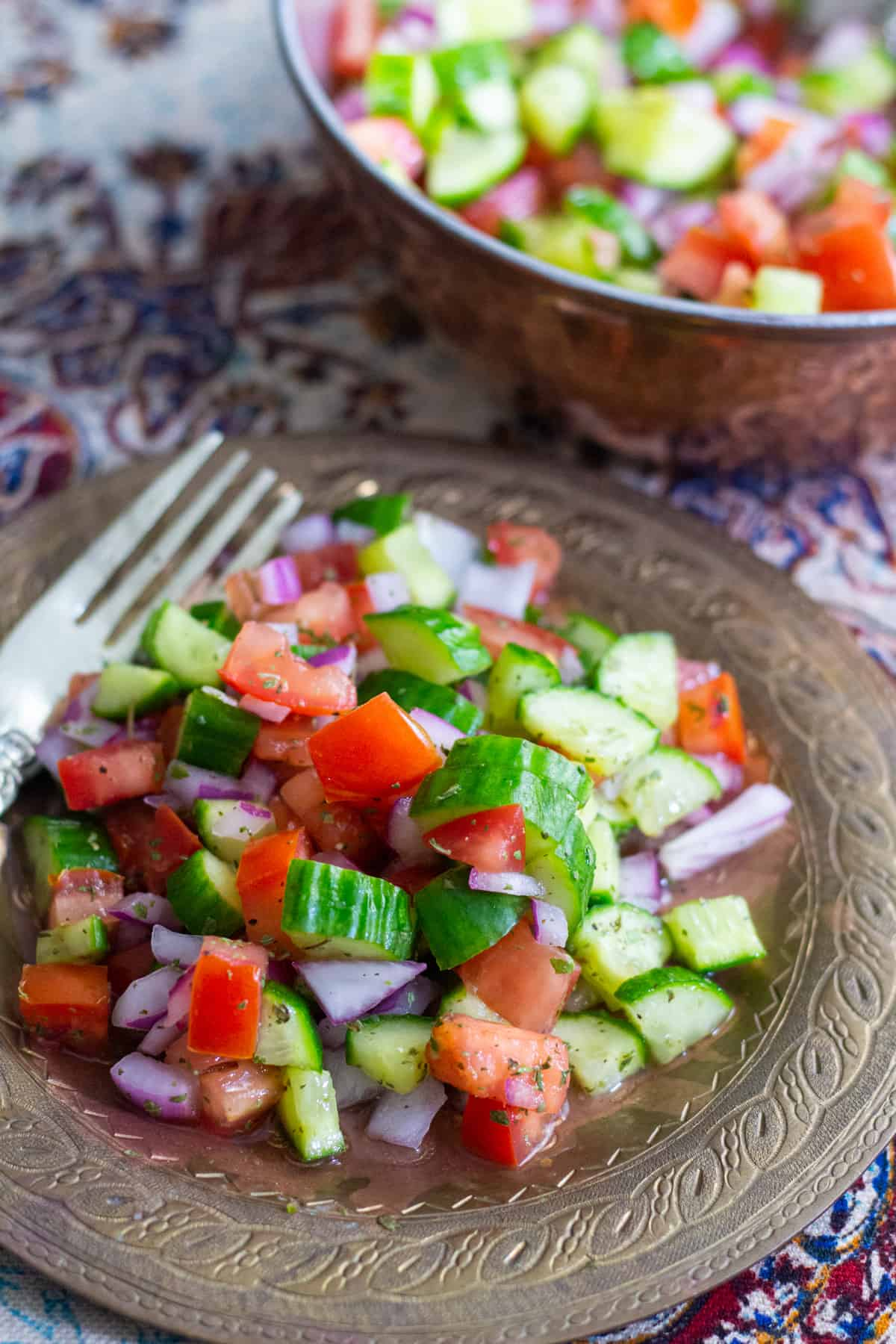 Persian salad shirazi served on a plate with a fork on the side.