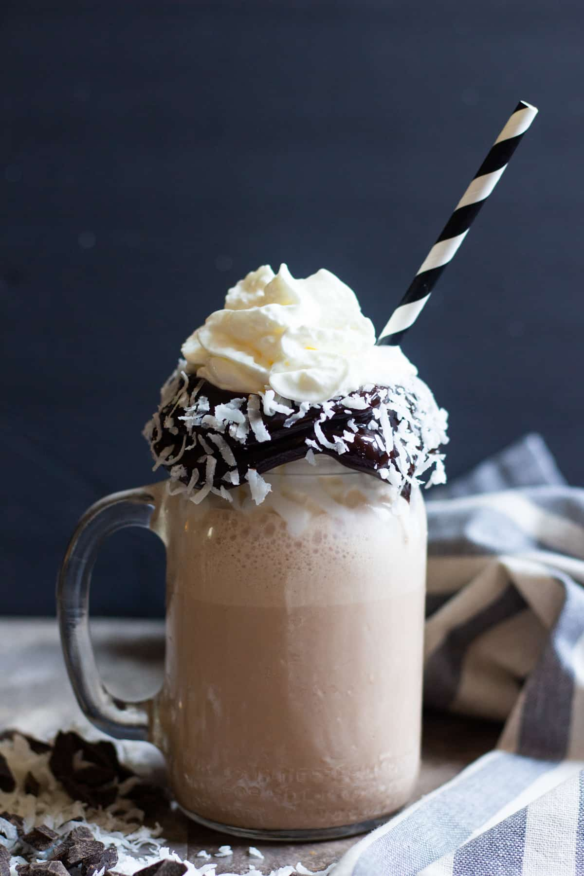 Delicious coconut milkshake poured into a glass topped with whipped cream.