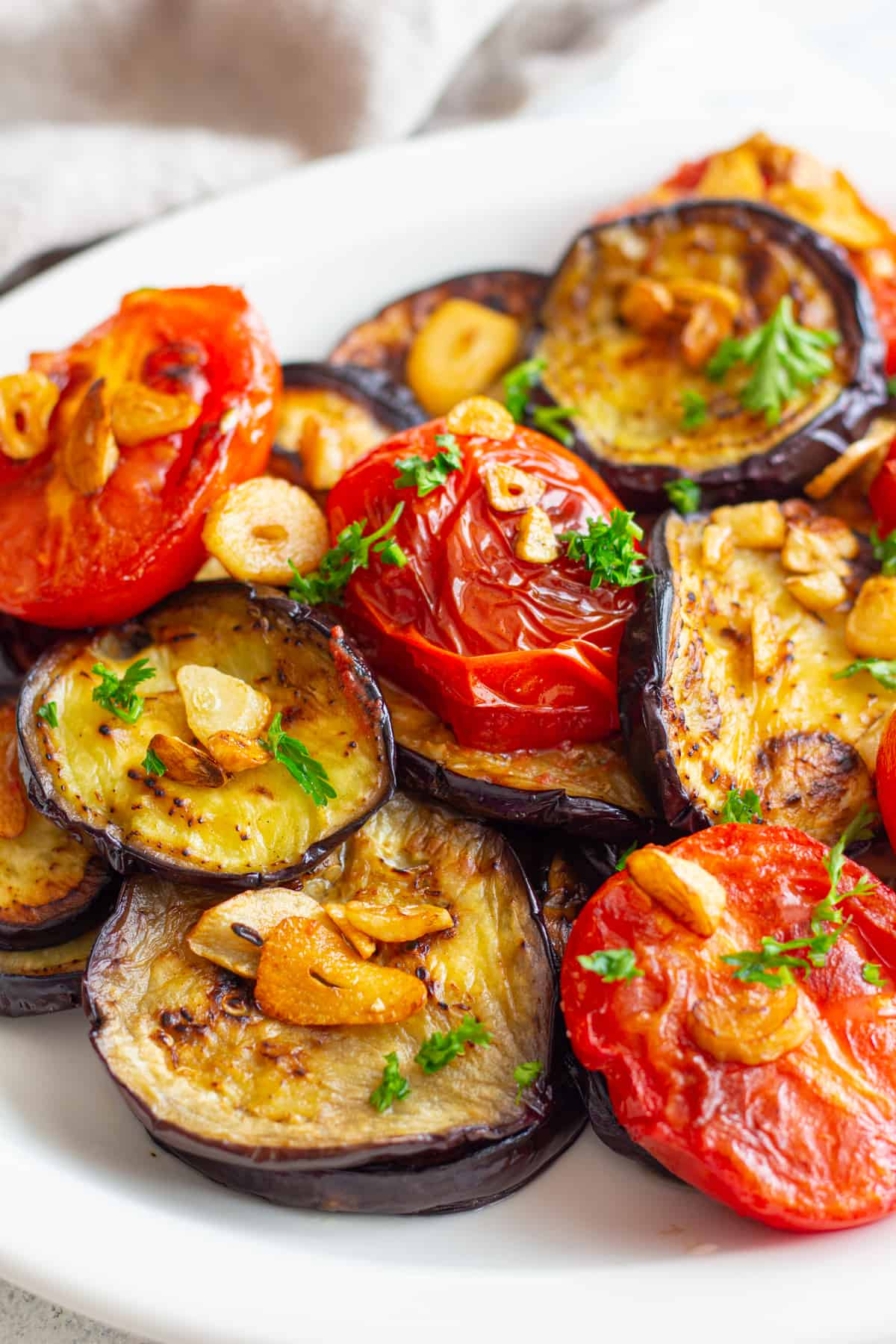 fried eggplant topped with tomatoes and garlic.