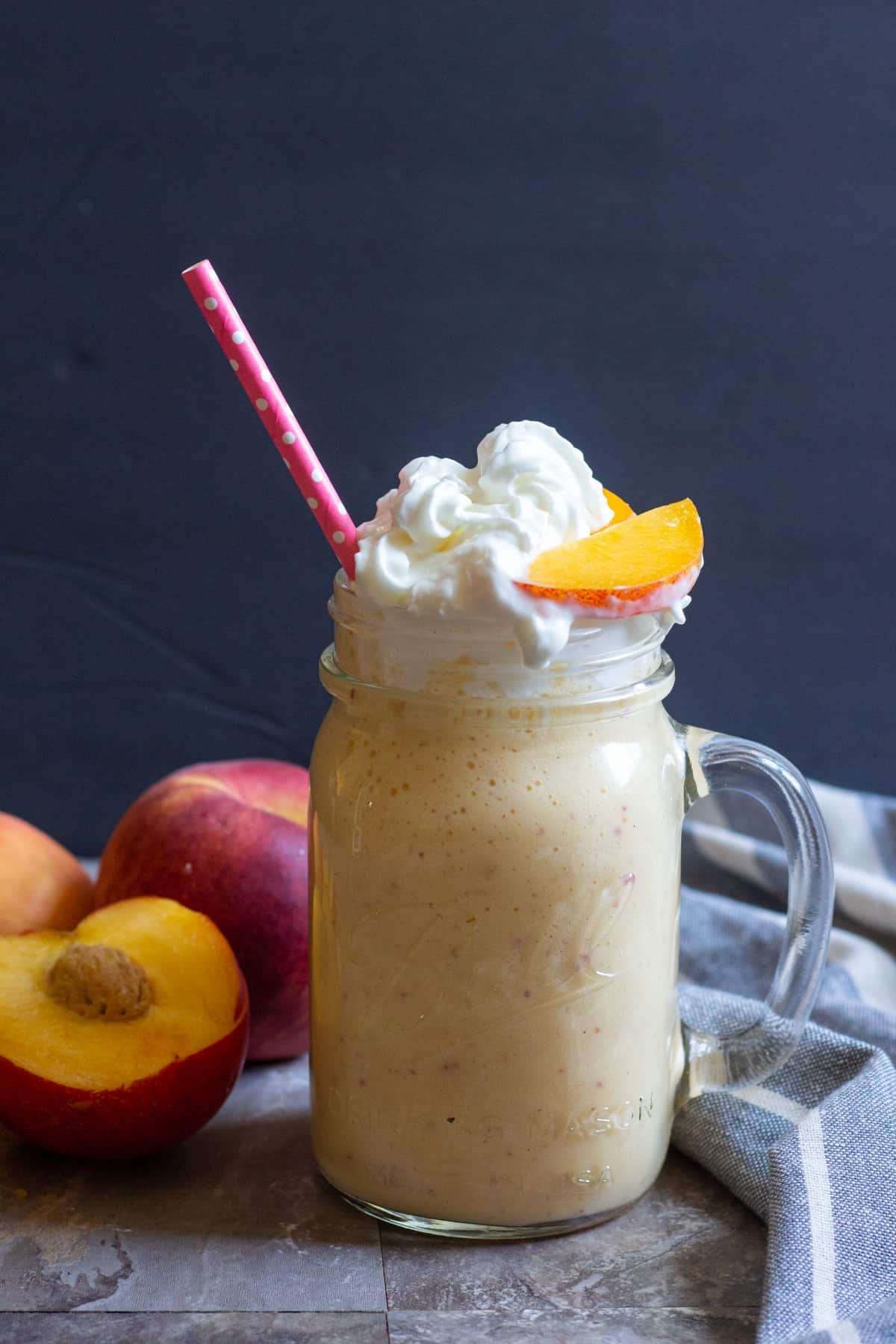 This easy milkshake recipe is perfect for kids and adults. Top with a slice of peach and drink with a straw.