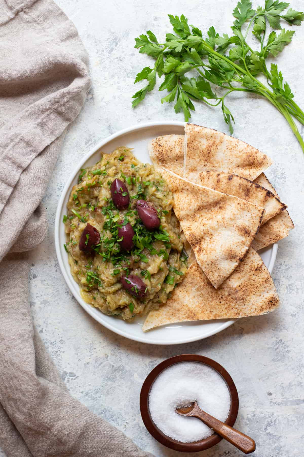 a plate of eggplant dip topped with olives and served with pita.
