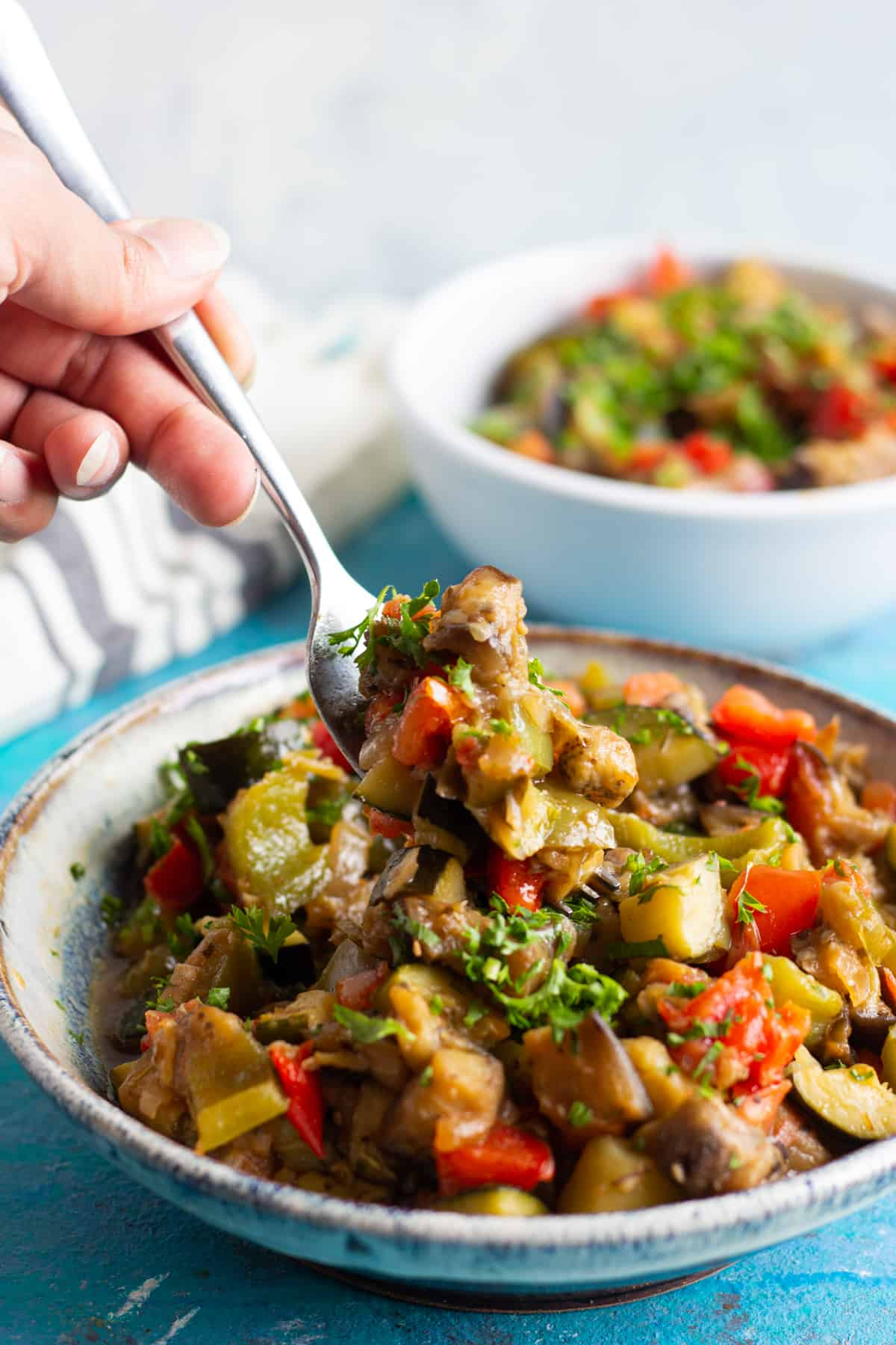 Mediterranean stew made with summer vegetables. Served in a bowl and with a fork.