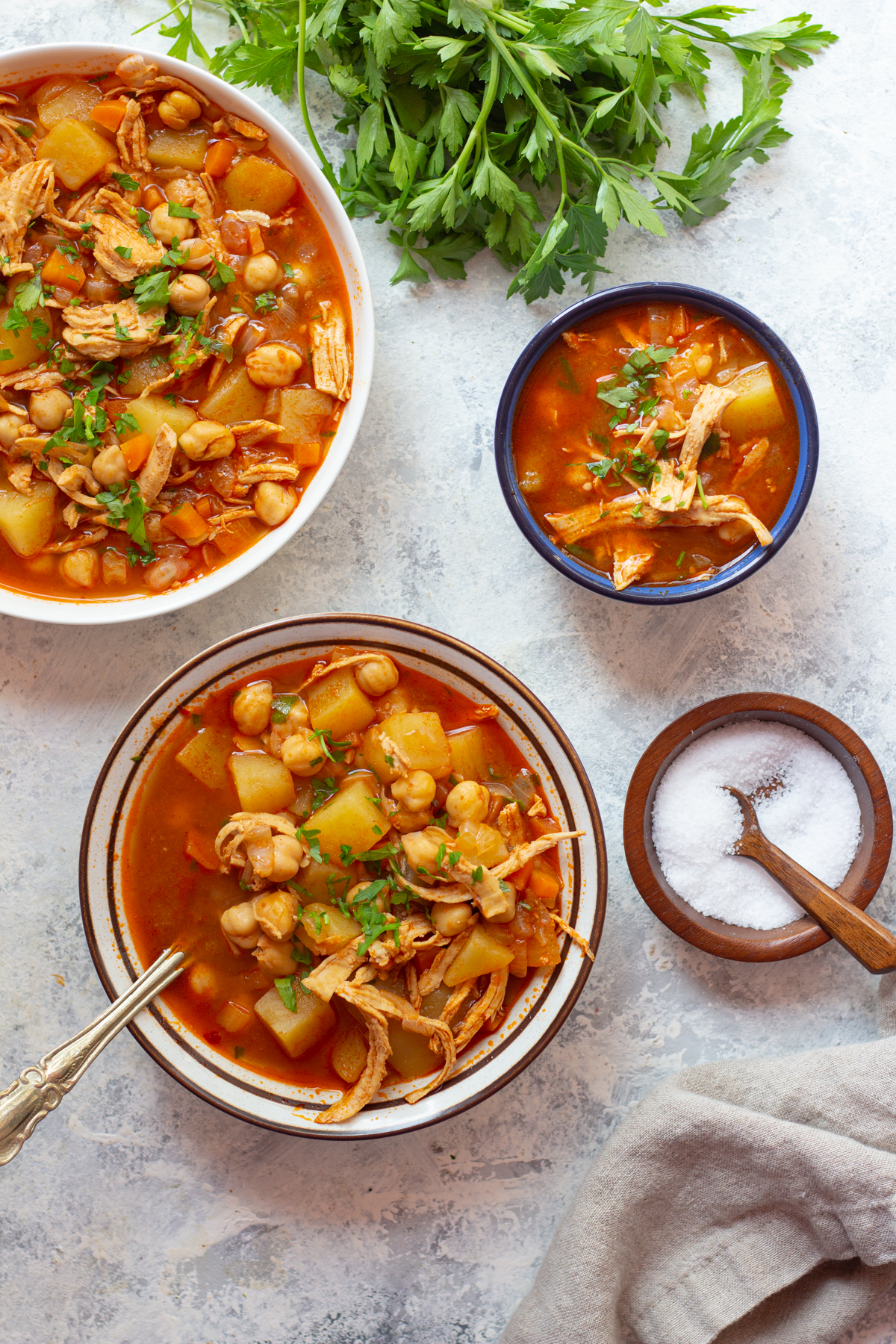 three bowls of chicken soup made with middle eastern spices.