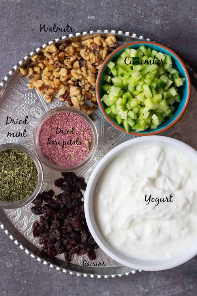 To make this yogurt dip we need cucumbers, yogurt, walnuts, raisins, rose petals and dried mint.