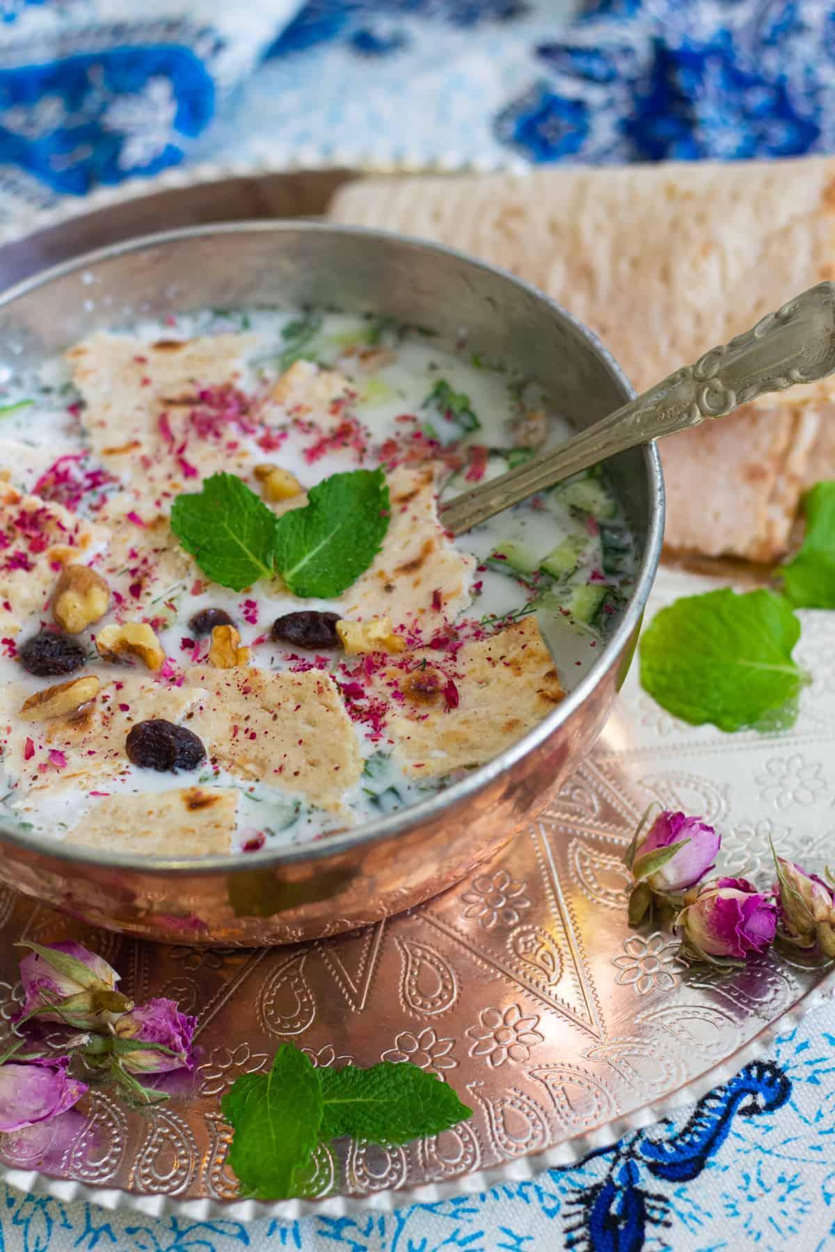 A bowl of yogurt soup with walnuts.
