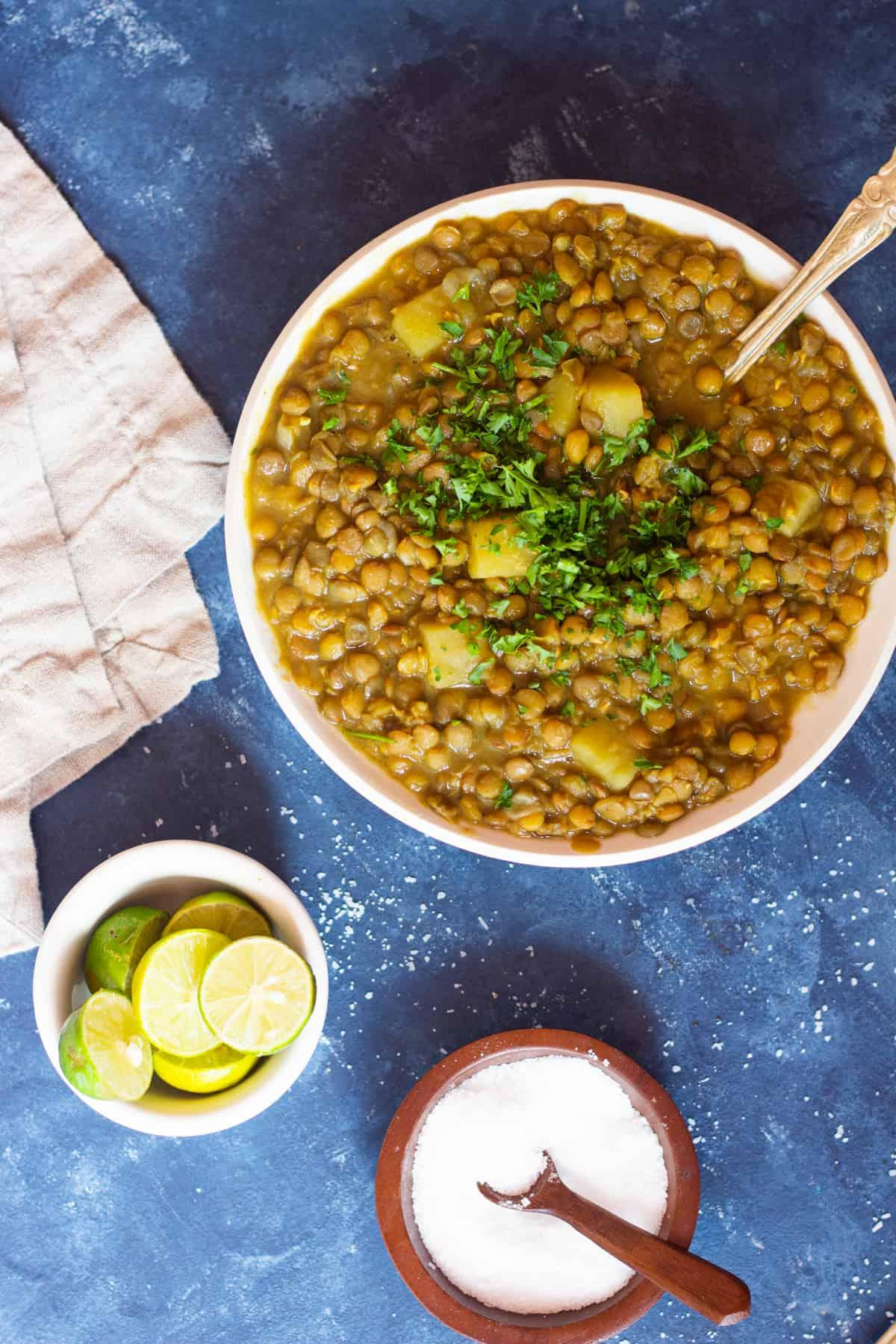 A bowl of lentil soup with lime juice.