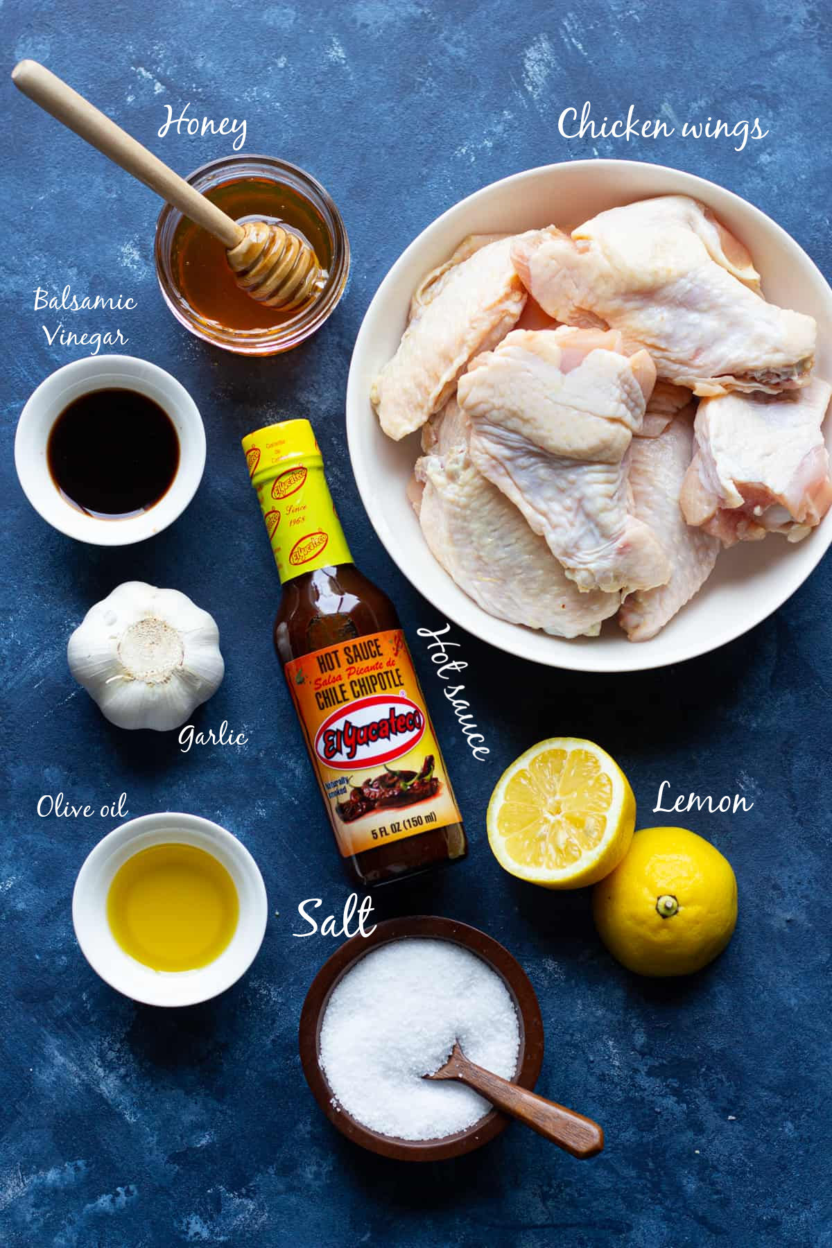Ingredients to make grilled chicken wings are honey, balsamic, lemon, hot sauce, salt, garlic and olive oil.
