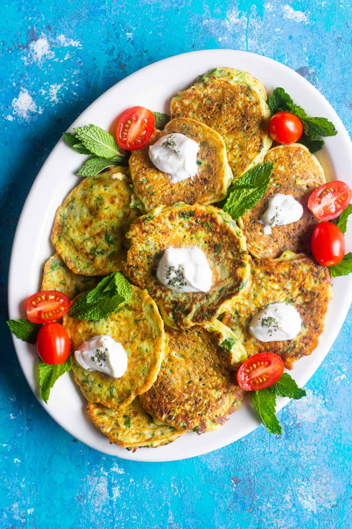 A plate of zucchini fritters topped with yogurt.