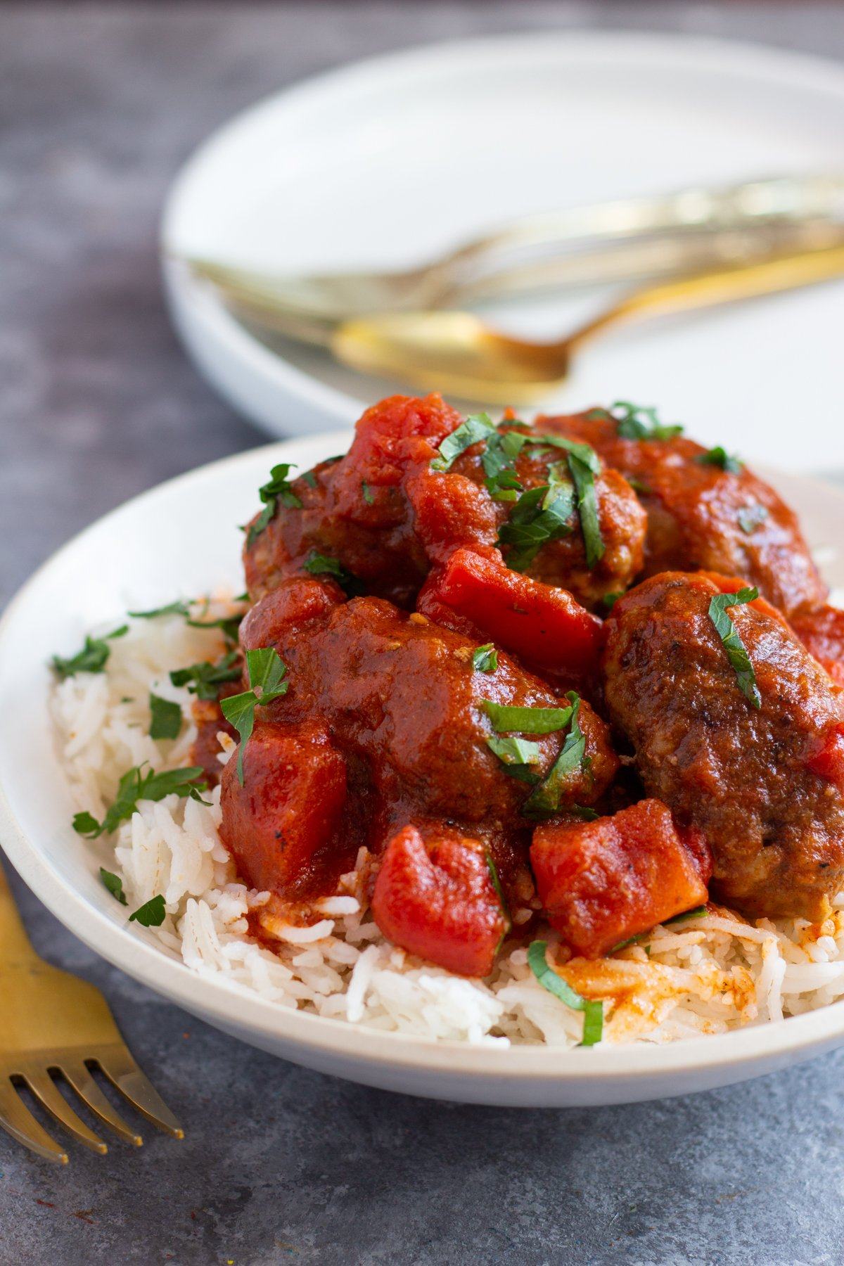 Soutzoukakia are Greek style meatballs cooked in a delicious tomato sauce. These meatballs are juicy thanks to a simple technique and are perfect with some rice, potatoes or even pasta. Learn how to make juicy meatballs every time with my simple method! This is a super easy dinner recipe that everyone loves!