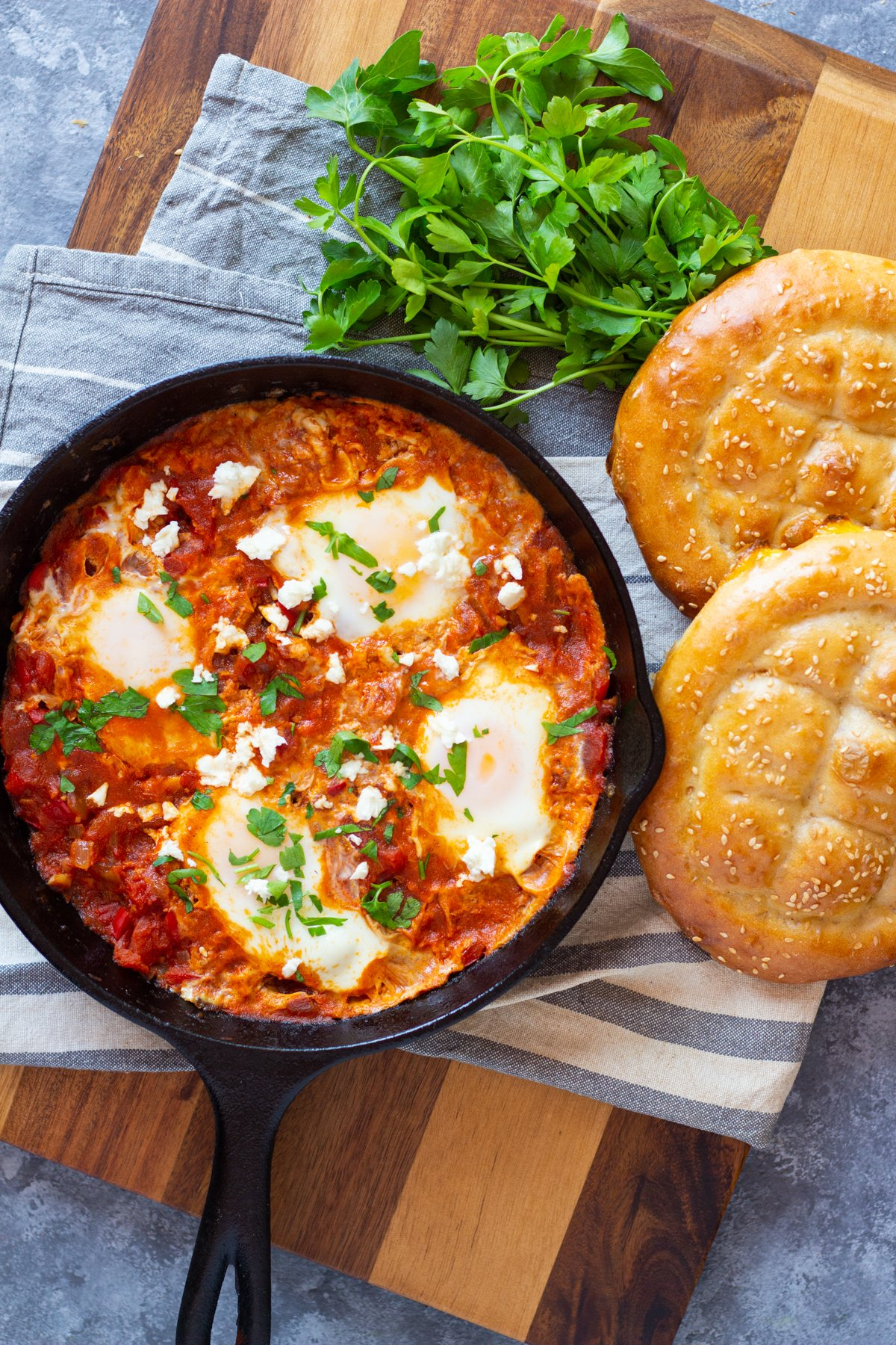 Overhead shot of the poached eggs in tomato sauce in a pan with bread and parsley.