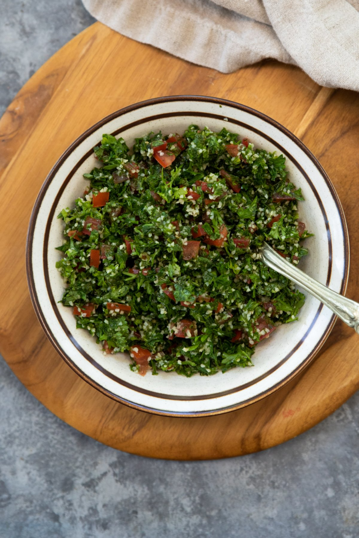 a bowl of tabbouleh salad on a wooden board.